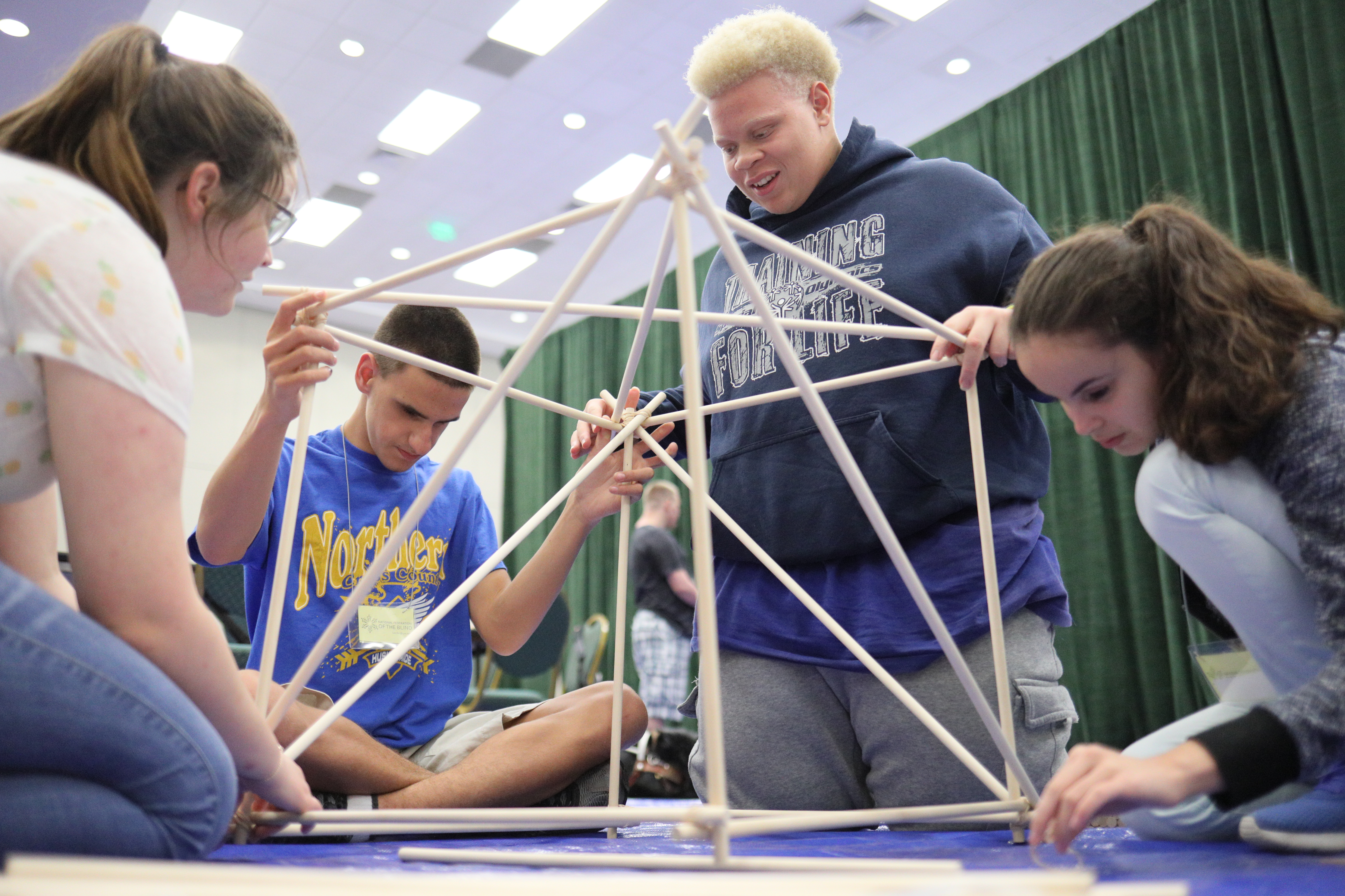 Photo of students working together to build a structure out of large wooden dowels.
