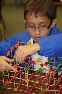 A blind student builds a bridge using toothpicks and gumdrops.
