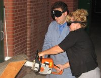A JSA parent under sleepshade uses a chainsaw to cut through a log with the assistance of Mark Riccobono.