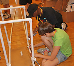 Teens construct a track, out of PVC pipe, for their blind-drivable hovercraft.