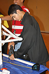 A young man cuts a piece of PVC pipe to length; it will be used to construct a prototype of a spacecraft.